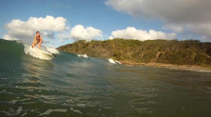 Catherine qui surf les vagues de Airlie beach en Australie.